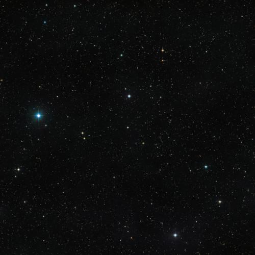 Il cielo attorno alla stella doppia V471 Tauri, visibile con bassa luminosità al centro dell'immagine (Immagine ESO/Digitized Sky Survey 2)