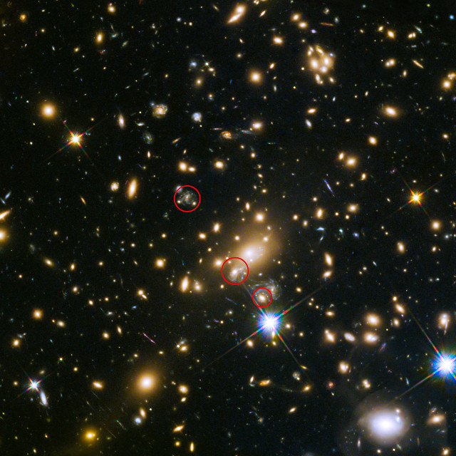 Immagine che mostra le apparizione della supernova SN Refsdal. Nel cerchio in alto una possibile apparizione nel 1998, in quello centrale l'apparizione del 2015 e in quello in basso l'apparizione del 2014 (Immagine NASA, ESA, S. Rodney (John Hopkins University, USA) and the FrontierSN team; T. Treu (University of California Los Angeles, USA), P. Kelly (University of California Berkeley, USA) and the GLASS team; J. Lotz (STScI) and the Frontier Fields team; M. Postman (STScI) and the CLASH team; and Z. Levay (STScI))