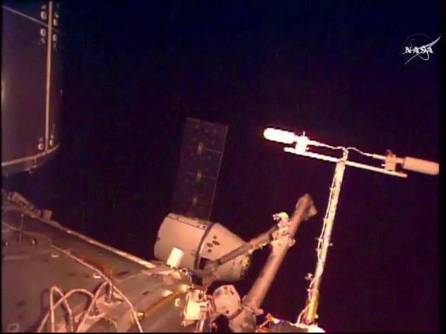 La navicella spaziale Dragon catturata dal braccio robotico della Stazione Spaziale Internazionale (Immagine NASA TV)