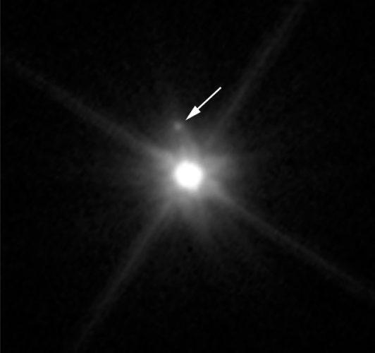 Il pianeta nano Makemake visto dal telescopio spaziale Hubble con la sua luna indicata dalla freccia (Immagine NASA, ESA, and A. Parker and M. Buie (SwRI))