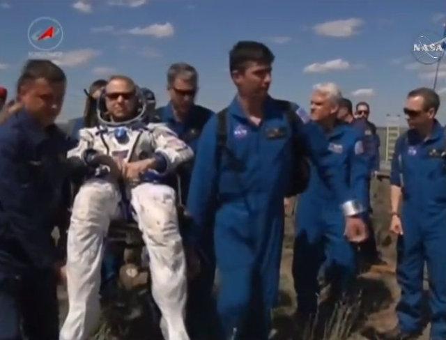Tim Kopra assistito dal personale dopo l'atterraggio (Immagine NASA TV)