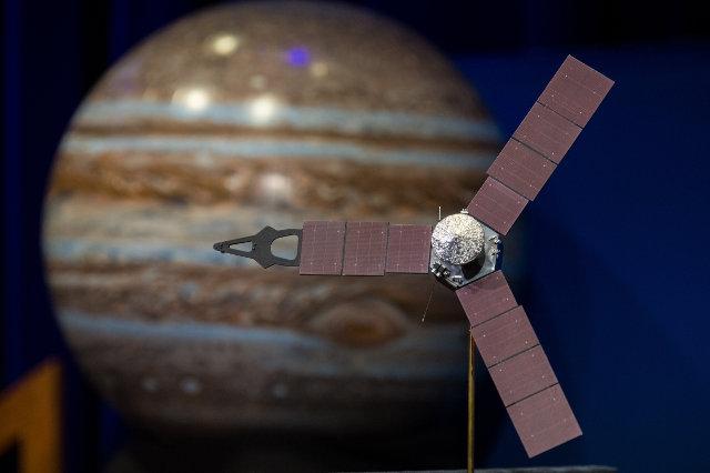 Un modellino della sonda spaziale Juno con un'immagine di Giove sullo sfondo (Foto NASA/Aubrey Gemignani)