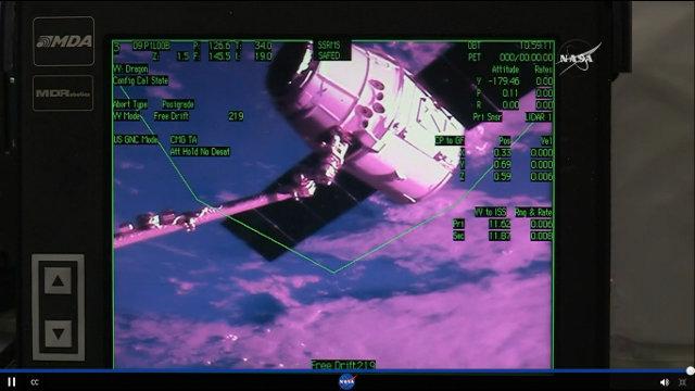 La navicella spaziale Dragon catturata dal braccio robotico della Stazione Spaziale Internazionale nella missione CRS-9 (Immagine NASA TV)