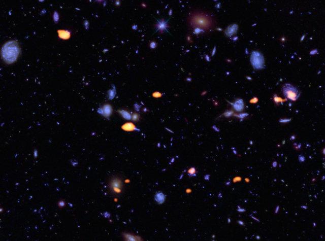 Galassie ricche di monossido di carbonio indicate in arancione assieme a quelle già viste da Hubble in blu (Immagine B. Saxton (NRAO/AUI/NSF); ALMA (ESO/NAOJ/NRAO); NASA/ESA Hubble)