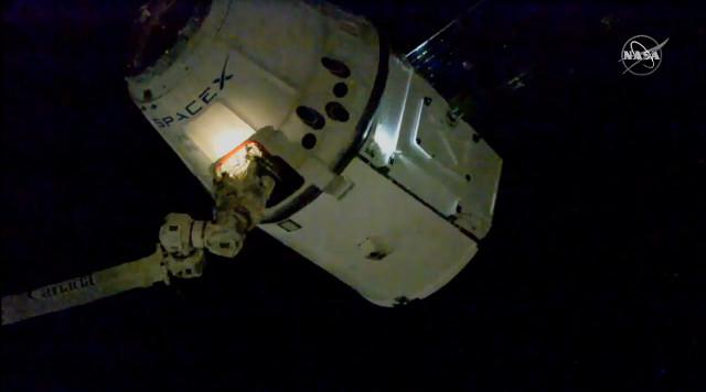 Il cargo spaziale Dragon di SpaceX catturato dal braccio robotico Canadarm2 della Stazione Spaziale Internazionale nella missione CRS-19 (Immagine NASA TV)