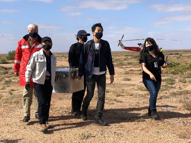 La capsula con i campioni dell'asteroidi Ryugu trasportati dal personale dopo il recupero (Foto cortesia JAXA)
